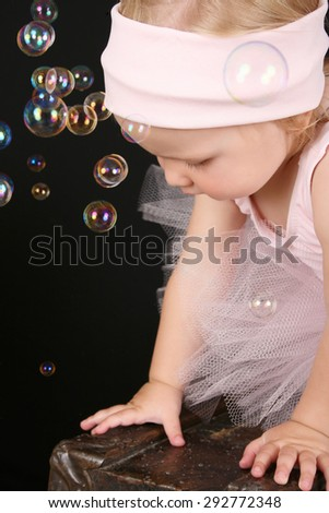 Blond girl wearing a ballet tutu playing with bubbles - stock photo