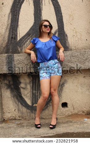 Blond girl wearing a blue dress posing on the wall - stock photo