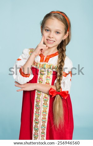 Blond girl with a scythe in the traditional Russian folk costume. Girl seven years. - stock photo