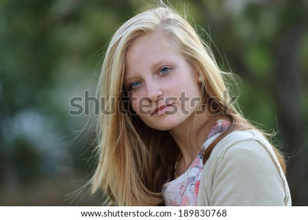 Blond girl with beautiful long straight hair on nature - stock photo