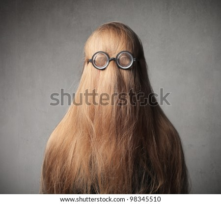 Blond girl with her hair on her face wearing eyeglasses - stock photo