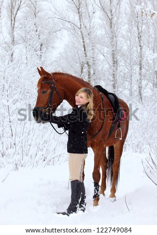 Blond girl with her horse in a snow landscape - stock photo