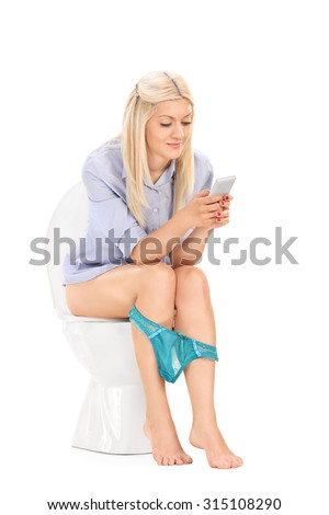 Blond girl with her panties down seated on a toilet and working on a cell phone isolated on white background - stock photo