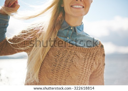 Blond girl with long hair and toothy smile showing satisfaction - stock photo
