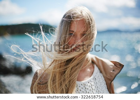 Blond girl with long hair looking at camera by the seaside - stock photo