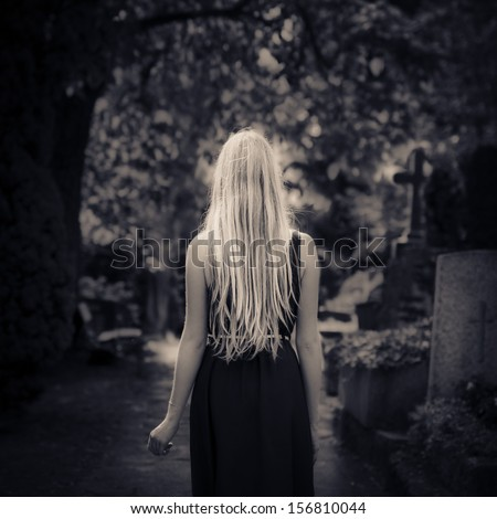 Blond girl with long hair walking alone in the dark at cemetery  - stock photo