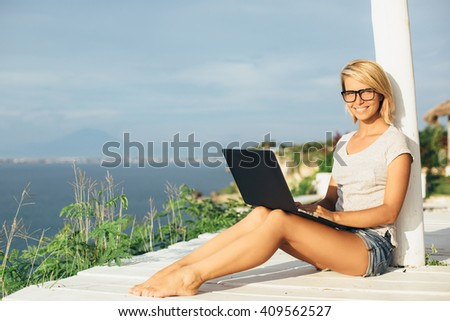 Blond girl working with a laptop on the tropical beach. Female freelancer working near the sea. Attractive blonde hair woman using laptop on the beach and smile. Distance learning