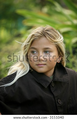 Blond green eyed pre-teen girl outdoors on green background