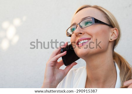 Blond hair girl sitting behind the table an talking by the phone