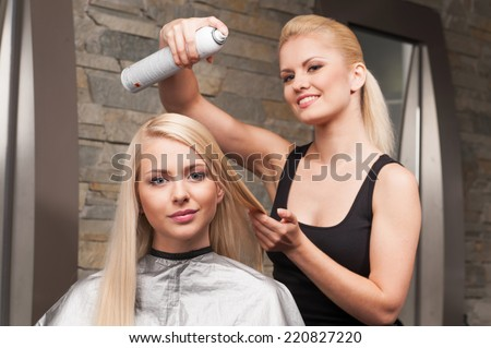 blond hairdresser applying spray on client's hair and looking into camera. Female hairdresser works on woman hair in salon - stock photo