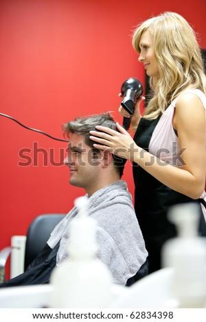Blond hairdresser drying her customer's hair in her salon - stock photo