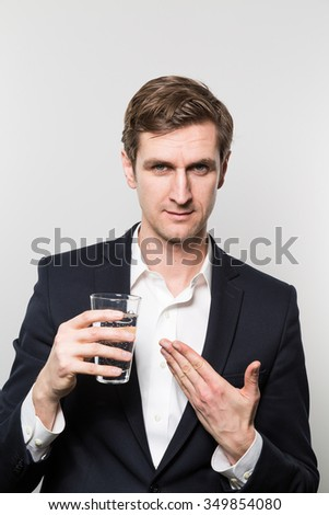 Blond-haired european businessman offers a glass of sparkling water with a satisfied look in front of a gradient background