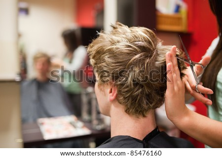 Blond-haired man having a haircut with scissors - stock photo