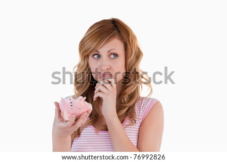 Blond-haired woman perplexed concerning her broken piggy bank on a white background