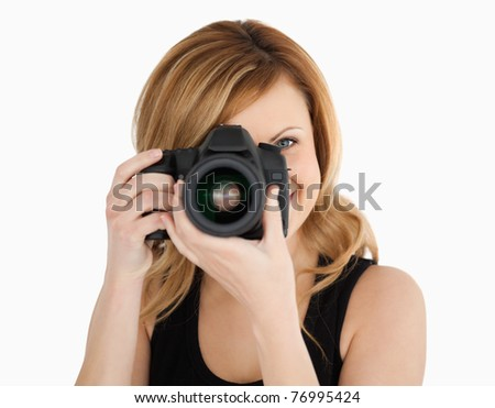 Blond-haired woman taking a photo with a camera on a white background