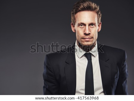 Blond handsome young man looking at camera with a serious and determined facial expression while wearing business black suit, white shirt and tie, portrait with copy space on grey - stock photo