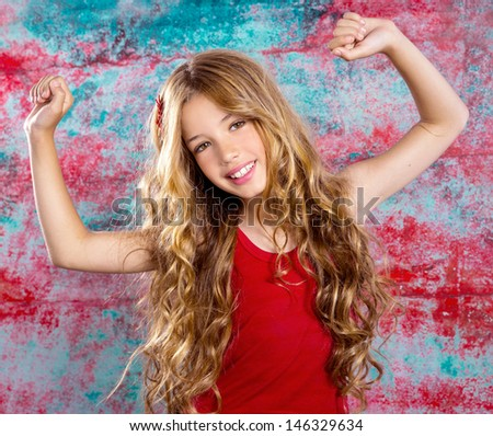 Blond happy children girl in red happy with arms up in grunge background - stock photo