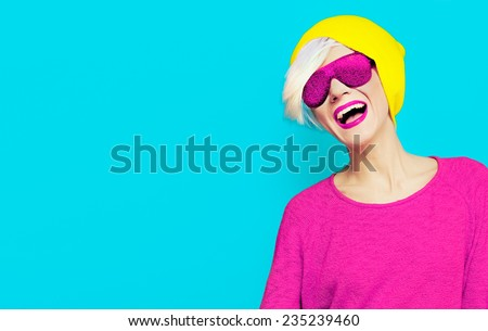 Blond happy girl with a stylish Cap and Sunglasses on bright background - stock photo