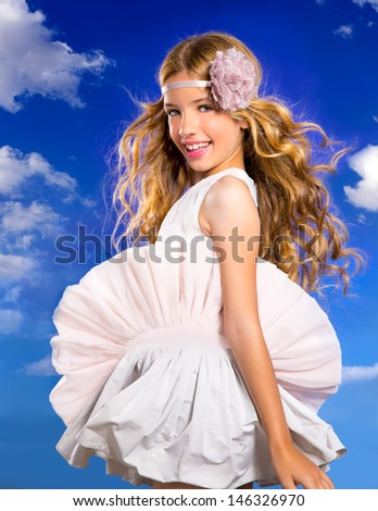 Blond happy girl with fashion dress and wind blowing hair in a blue sky background - stock photo