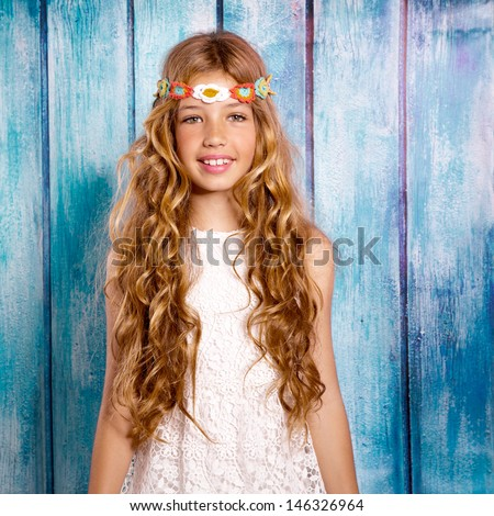 Blond happy hippie children girl smiling on blue grunge wood background - stock photo