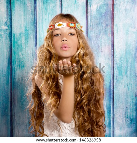 Blond hippie children girl blowing mouth with hand on blue grunge wood - stock photo