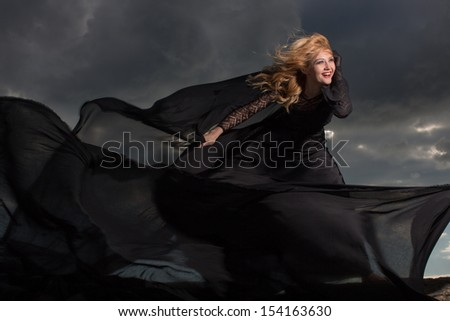Blond in a long black dress stand against the background of gray clouds