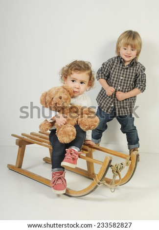 blond infant girl seating on the vintage wooden sledge with her teddy bear and blond little boy jumping behind her
