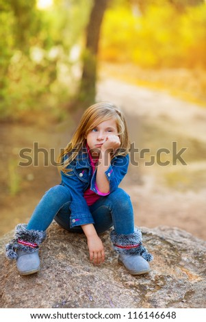 blond kid girl pensive bored expression in the forest outdoor sitting on a rock - stock photo