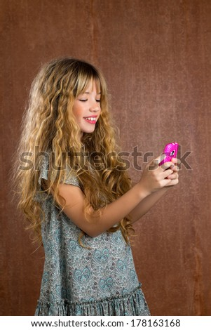 Blond kid girl playing with mobile smartphone portrait on vintage background - stock photo