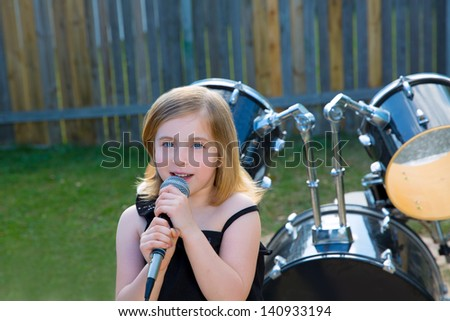 Blond kid girl singing in the backyard with drums behind - stock photo