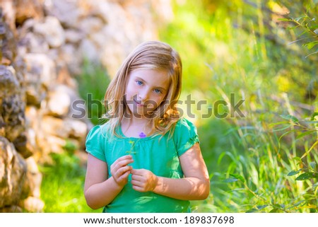 Blond kid girl smiling with purple flower relaxed in green outdoor