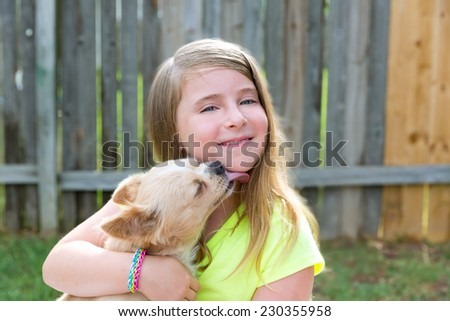 Blond kid girl with chihuahua pet dog kiss playing happy outdoor - stock photo