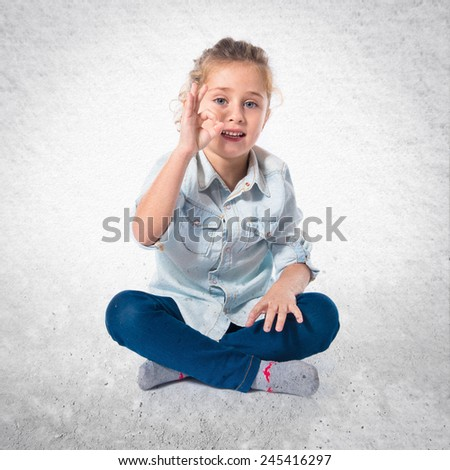 Blond kid making Ok sign
