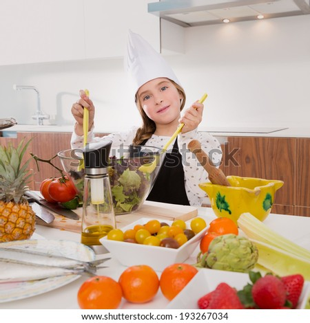 Blond kind girl junior chef on countertop preparing salad - stock photo