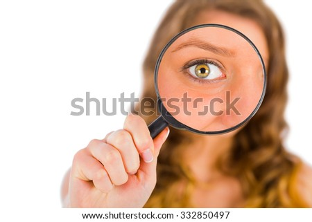 Blond lady holding a magnifying glass focused on her green eyes.