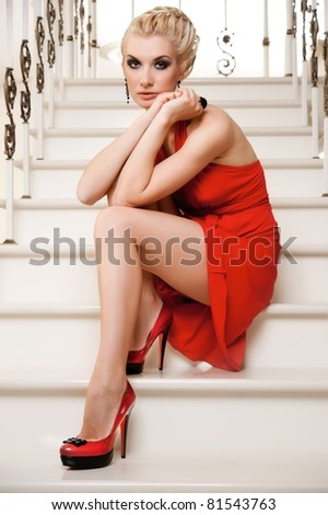 Blond lady sitting on a stairs