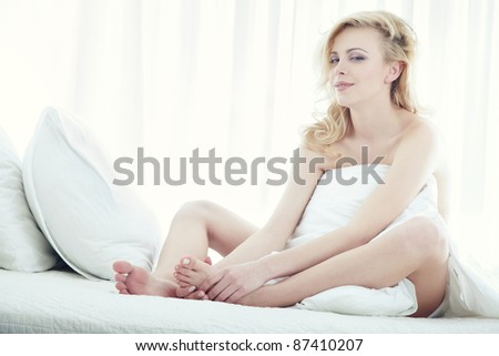 Blond lady sitting on the bed in spa room