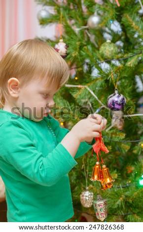 blond little boy dresses up Christmas tree toys - stock photo