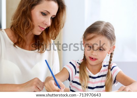Blond little girl hold in arm pencil drawing something together with mom. Beautiful female young artist, minor baby-sitter, art joy, juvenile development, parent lifestyle, youth, painter concept