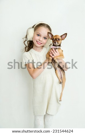 blond little girl holds small pet dog.  - stock photo