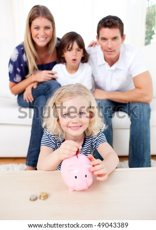 Blond little girl inserting coin in a piggybank in the living room - stock photo