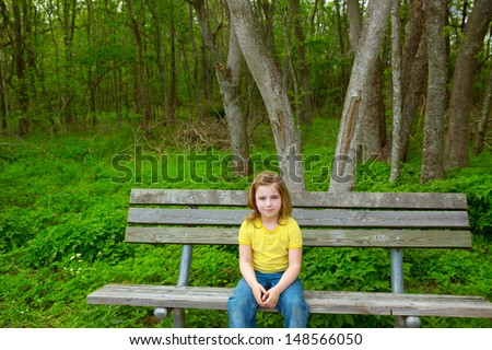blond lonely children girl happy sitting on park bench on forest jungle - stock photo