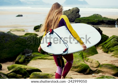 Blond long-haired girl dressed in wetsuit walking to the ocean ready to surfing, female surfer holding copy-space surfboard - stock photo