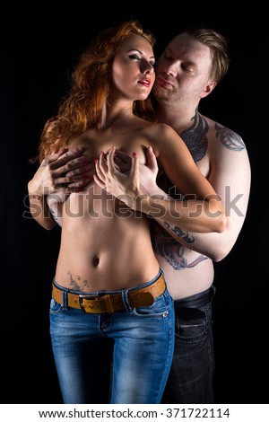 Blond man covering woman's breast on black background