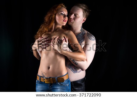 Blond man covering woman's chest on black background