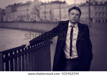 Blond man in a raincoat. Embankment. Romantic image. St. Petesburg. Lilac colour graded.