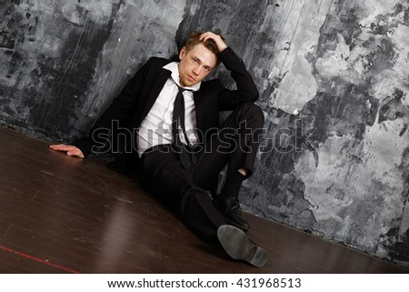 Blond man in depression sitting on the floor. Dressed in a formal classic suit