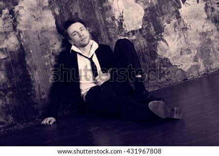 Blond man in depression sitting on the floor. Dressed in a formal classic suit. Antique colour graded.