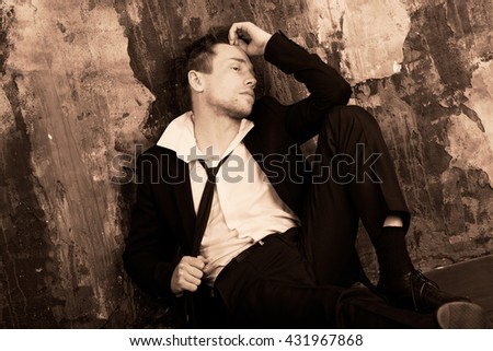 Blond man in depression sitting on the floor. Dressed in a formal classic suit.  Sepia colour graded.