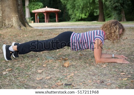 Blond middle aged woman outside doing stretching